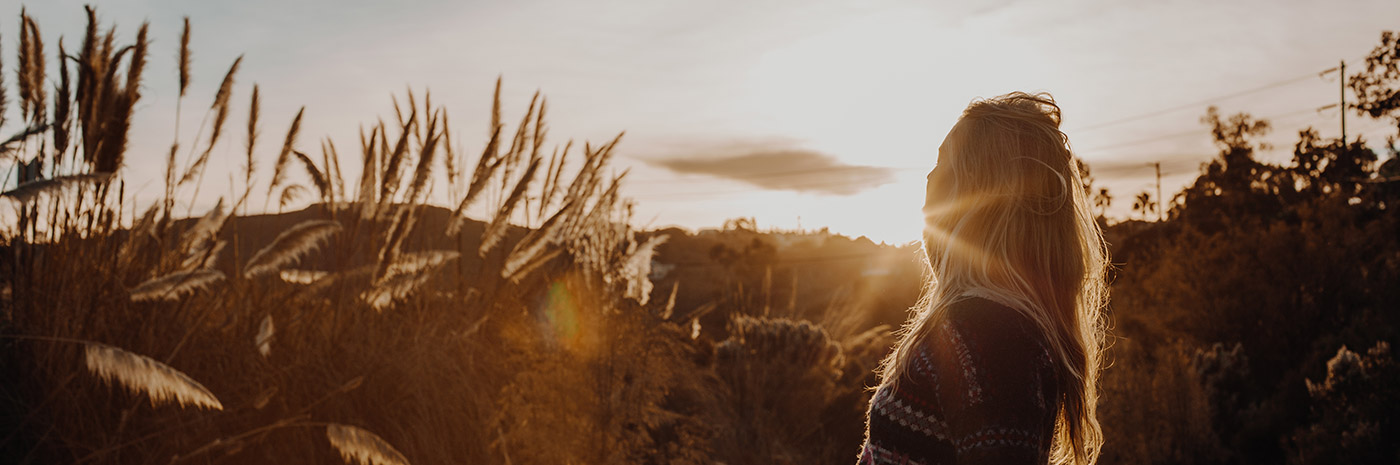 Woman in sweater standing outdoors in tall grass and brush lit by bright sunset light.