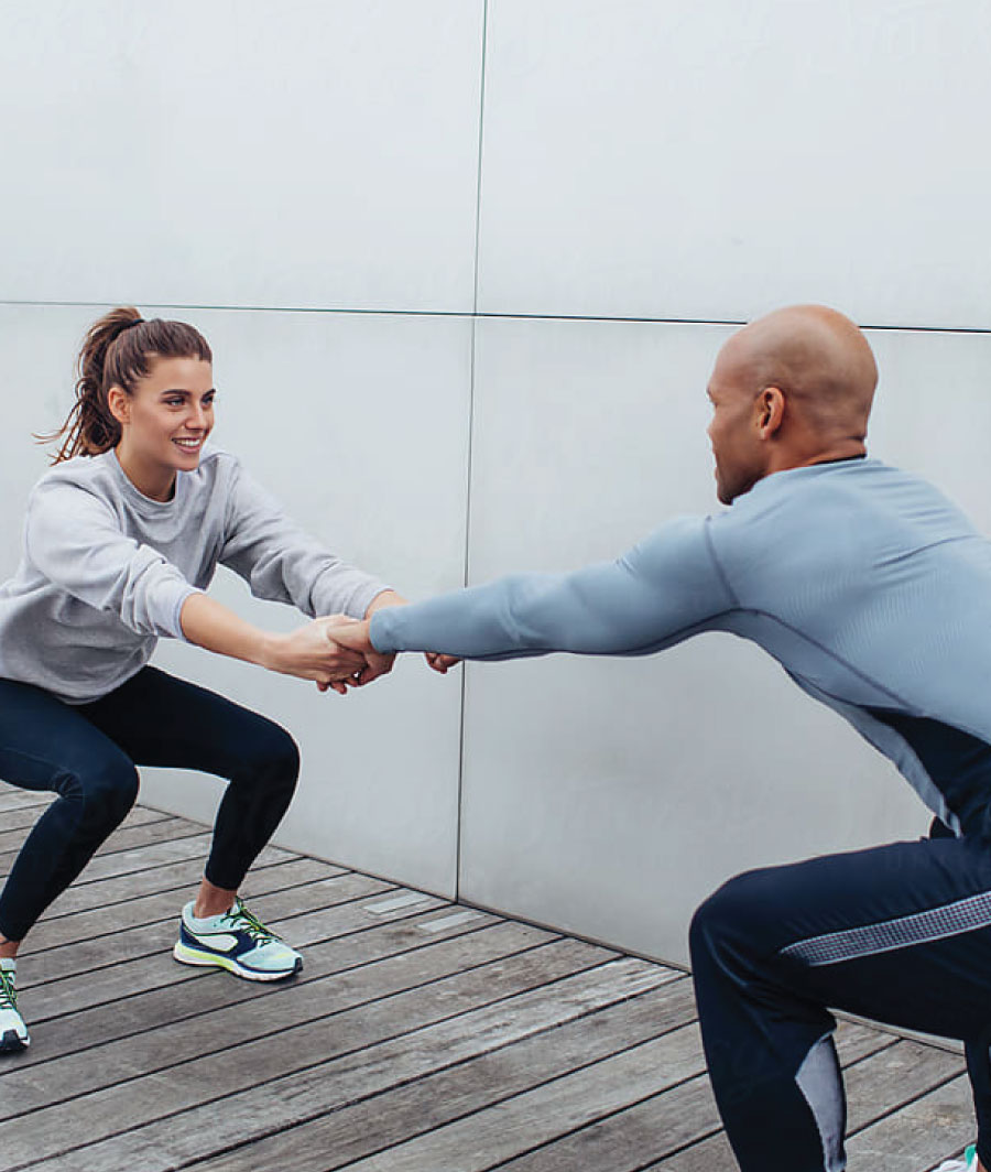 Man and woman in athletic clothing exercise together outdoors.