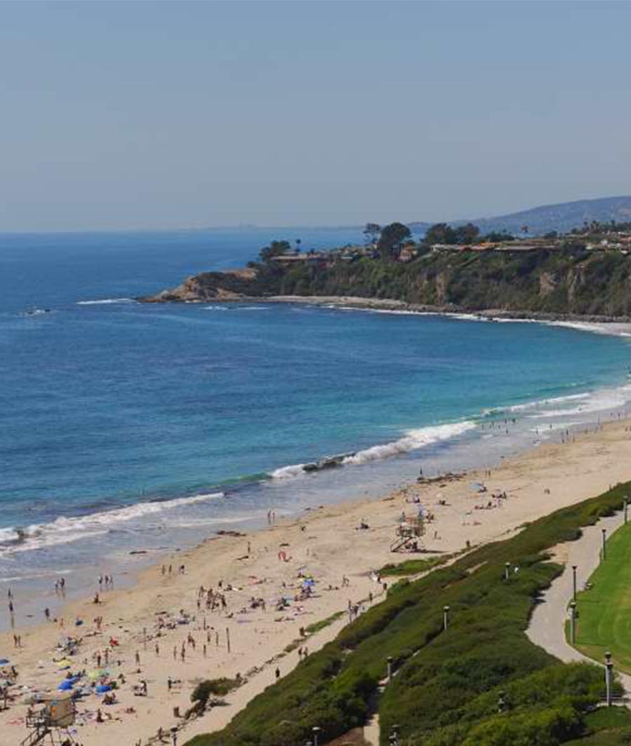 Bright blue ocean and sandy beach filled with people with nearby cliffs covered in green bushes.